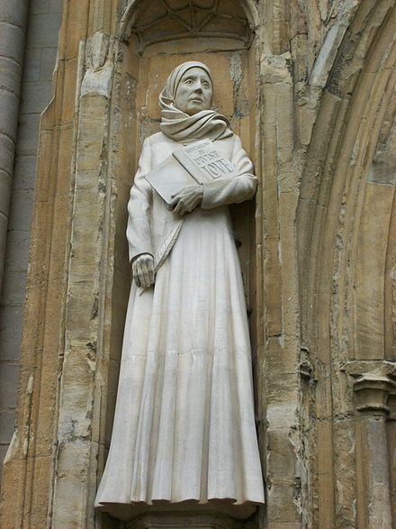 Statue of Julian on the front of Norwich Cathedral, holding the book Revelations of Divine Love